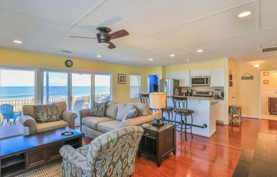 Living Room - Enjoy a sweeping view of the ocean from the open living room, furnished with a comfy couch and 2 armchairs.