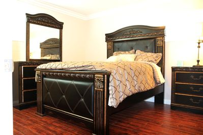 Master bedroom with queen size bed, dresser, mirror, night stand & night light