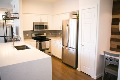 Light, bright kitchen w/ stainless steel appliances & quartz waterfall counter