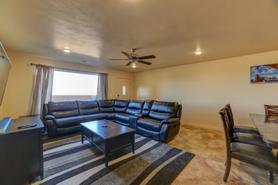 Open living room with power recliners and smart TV with cable.