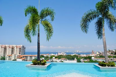 ROOF TOP INFINITY EDGE POOL WITH VIEWS OF THE CATHEDRAL, OLD TOWN AND THE BAY.