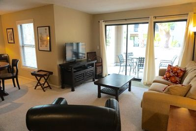 Bright living room with flat screen TV. Enjoy eating on patio.