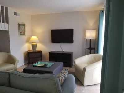 Comfy couch in living room , Flatscreen TV, Nice light from sliding glass doors.