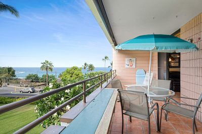 Covered lanai with patio table, chairs, & umbrella overlooking ocean