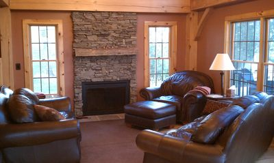 Great room with pine flooring, authentic fireplace, and leather furniture.