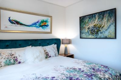 Master bedroom with incredibly comfortable King Bed surrounded by beautiful artwork