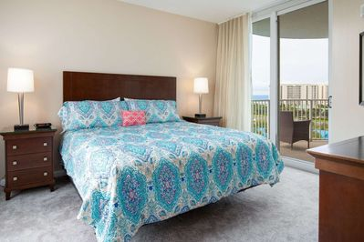 Carpeted master bedroom with king bed, dual nightstands and lamps, private access to balcony overlooking pools and Gulf