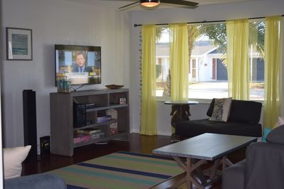 View into living room and outdoors. Great beach hues, seating and entertainment.
