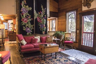 Living room facing fireplace with couch and needlepoint hangins