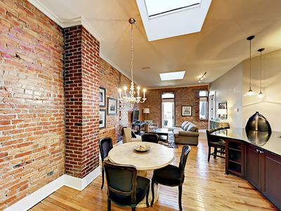 Dining Area - High ceilings with skylights, exposed brick, and original hardwood floors fill this beautifully renovated apartment with sophisticated style.