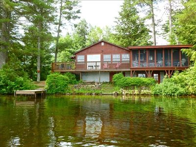 Sliding doors lead to balcony next to screened porch with beautiful lake view.