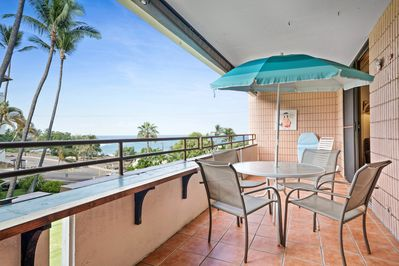 Patio table and 4 chairs with blue umbrella on covered lanai