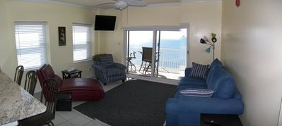 Living room w/ view to the east and south. Wall mounted HD LED flat screen TV.