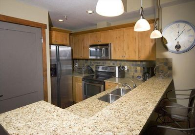 Immaculate full kitchen with stainless steel appliances and granite countertop