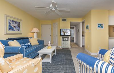 Bright and open living room with sleeper sofa, flat screen TV and DVD.
