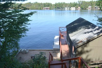 View front the top deck looking down over boathouse, beach and lake.