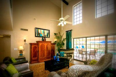 Main living room w/super high ceilings, views out to pool, golf course, pond etc