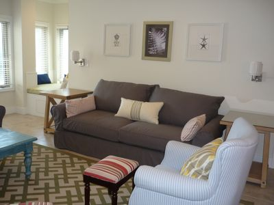 Bright, newly decorated living room with cozy window seat overlooking beach.
