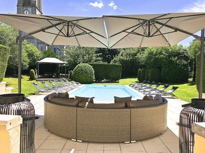 Rear garden and pool area with shaded seating and sunloungers