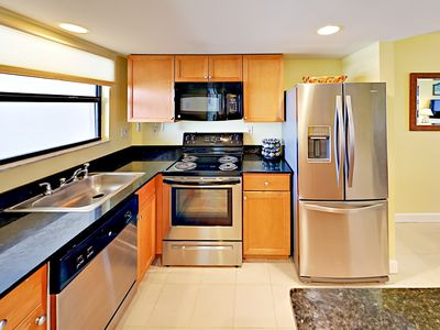Kitchen - Granite countertops, stainless steel appliances, and rich wood cabinets await in the kitchen. TurnKey stocks a starter supply of dish soap and paper towels.