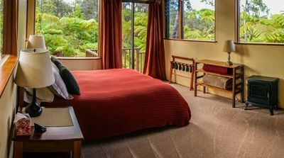 Spacious bedroom with several large picture windows and comfortable queen bed.