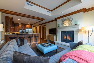 The living area is a part of an open concept room that includes the kitchen and dining areas.