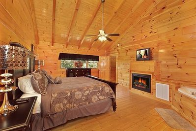 Large master bedroom with fireplace and jacuzzi tub.