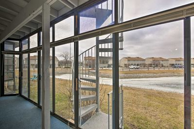 This vacation rental condo has an enclosed porch and views of the pond!