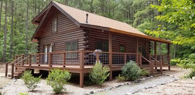 Beautiful log cabin set with a forest backdrop.