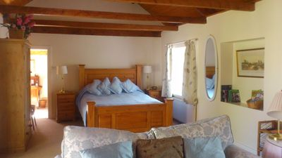 Marian Cottage King bed (5') in open-plan bedroom/living area.  Vaulted ceiling