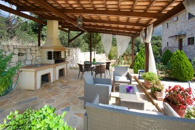 Lounge-Dining area outside shaded by a pergola, with BBQ and outdoor sink