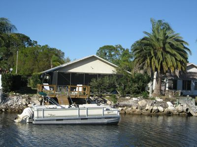 Peaceful home with screened-in heated pool, dock, and pontoon on canal.