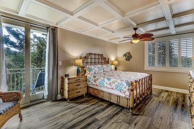 Spacious Master Bedroom with balcony, plantation shutters, & coffered ceiling