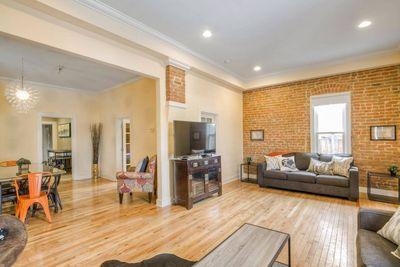 Spacious living room with exposed brick.