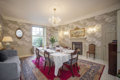 Dining room with sash window leading to wrought iron balcony and steps to courtyard