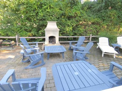 Very private back yard features this large, well furnished patio and fireplace.