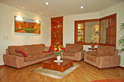 Spacious, inviting,and comfortable living room, brightly lit.