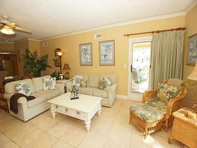 Living room with new pull-out couch, opens to balcony and has ocean view