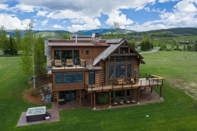 Home exterior with deck, patio, hot tub, and master balcony