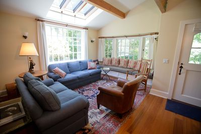 Sunny living room with a large skylight looking up into the oak tree
