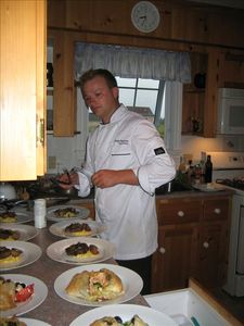 """Caterer """"plating"""" in kitchen"""