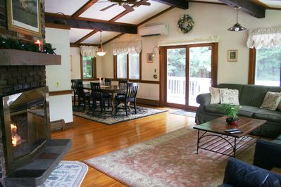 living room: view of dining area, deck, wood burning fireplace (note A/C units)