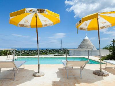 Photo for Complex of trulli with private pool overlooking the sea