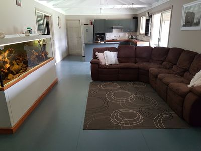 Lounge room and kitchen with tropical fish tank.