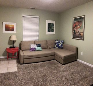 Living Room with fold-out couch and flatscreen tv hung on opposite wall.