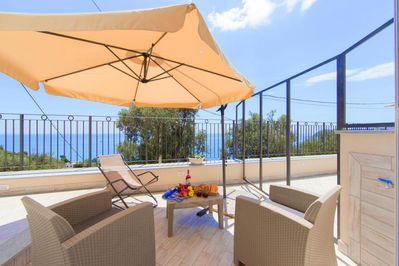 Outdoor terrace with chairs and sun ombrella