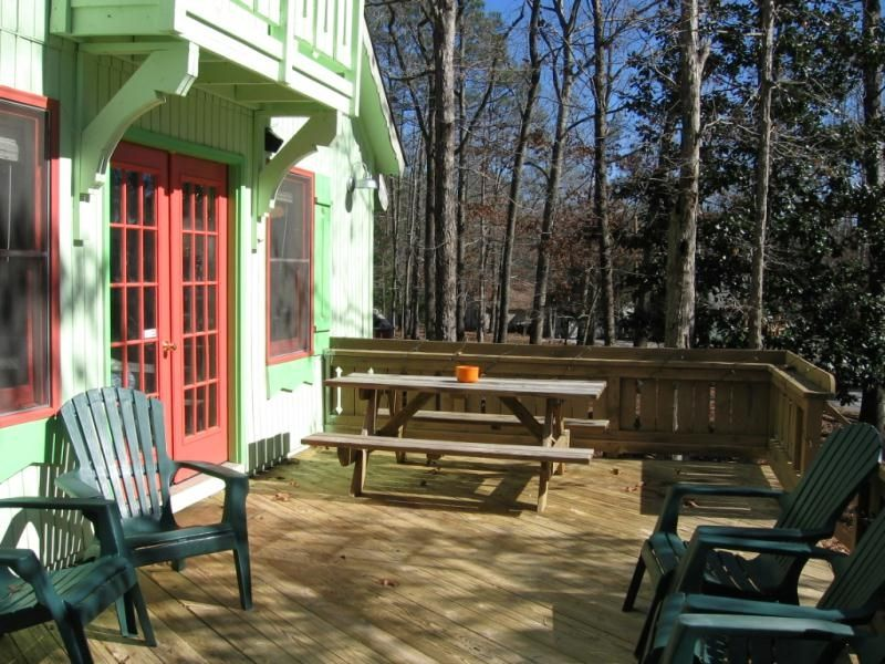 The Deck With Picnic Table And Adirondack Chairs.