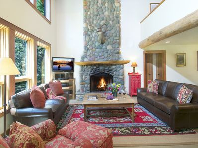 The living room with a large, river rock fireplace