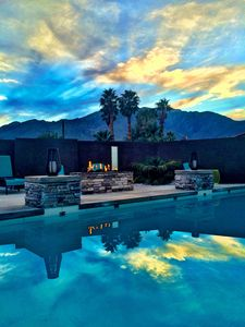 Pool area with beautiful sunsets, double waterfall feature, fire pit, optional heated pool, lounge and pool chairs