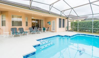 Pool deck with shaded lanai, 4 loungers, 4 chairs, large table, 2 side tables.